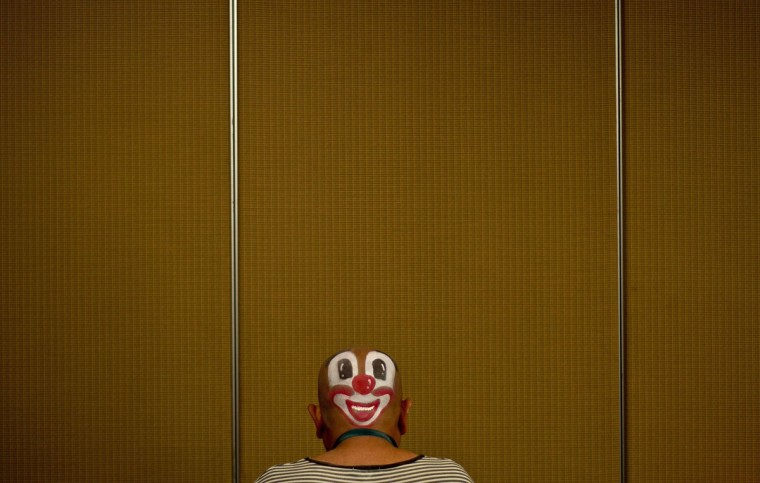 A clown prepares to take part in a Clown Festival in Kuala Lumpur on August 17, 2014. Around 80 clowns from all over Malaysia took part in the event organized by the Association of Clowns Malaysia to provide a platform for clown education, acquiring new skills and offering members support. (Manan Vatsyayana/AFP/Getty Images)