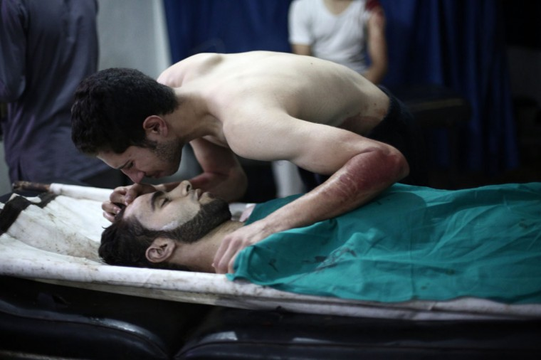A Syrian man kisses the body of his brother who was reportedly killed in a Syrian army airstrike on August 18, 2014 at a hospital in Douma, a rebel-held town near Damascus. Douma is a rebel bastion northeast of Damascus, which has been under suffocating army siege for more than a year. (ABD DOUMANY/AFP/Getty Images)