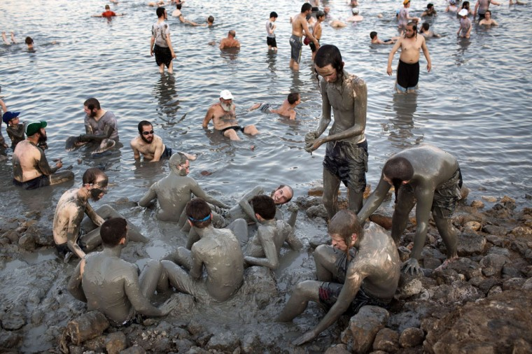 Ultra-Orthodox Jewish men and boys cover their bodies with mineral-rich mud during their vacation at a men's-only beach on the shores of the northern part of the Dead Sea on August 17, 2014. (MENAHEM KAHANA/AFP/Getty Images)