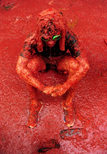 A man sits in tomato pulp at the end of the world's biggest tomato fight at La Tomatina festival on August 26, 2009 in Bunol, Spain. More than 45000 people from all over the world descended on the small Valencian town to participate in this year's La Tomatina festival, with the local town hall estimating that over 100 tons of rotten and over-ripe tomatoes were thrown. (Photo by Jasper Juinen/Getty Images)