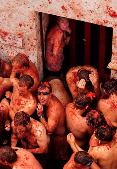 A girl shelters in the doorway of a house as revellers pelt each other with tomatoes during the world's biggest tomato fight at La Tomatina festival on August 26, 2009 in Bunol, Spain. More than 45000 people from all over the world descended on the small Valencian town to participate in this year's La Tomatina festival, with the local town hall estimating that over 100 tons of rotten and over-ripe tomatoes were thrown. (Photo by Jasper Juinen/Getty Images)