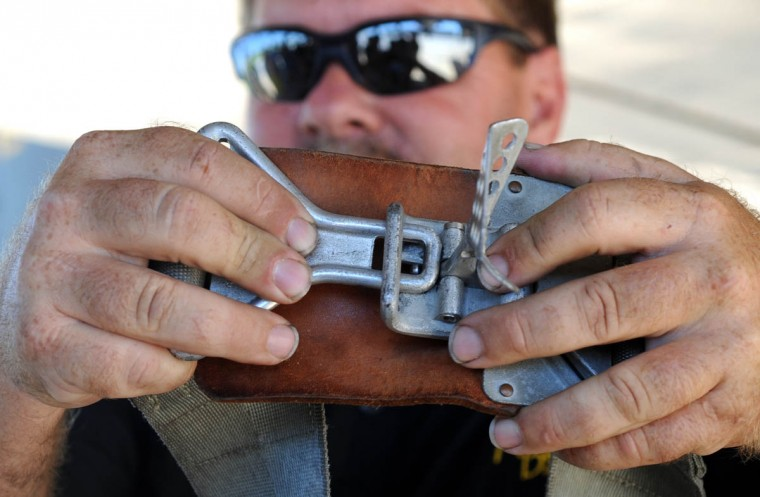 Crew chief John Eads demonstrates how to fasten the gunner's belt. (Algerina Perna/Baltimore Sun)