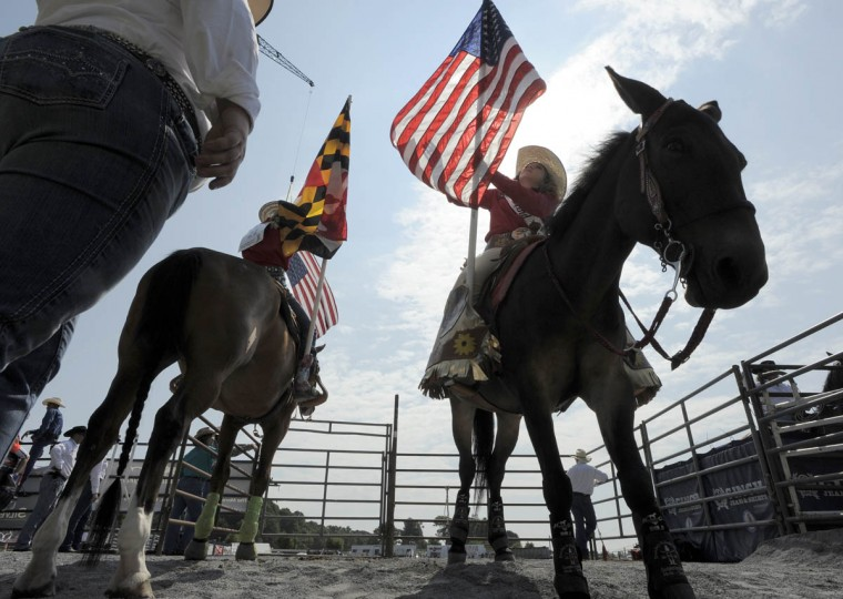 Maryland High School Rodeo Queen, Madison Iager lifts the American Flag as she gets ready for the opening ceremonies for the Maryland High School Rodeo at the Howard Fair. (Lloyd Fox/Baltimore Sun)