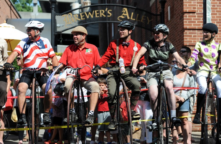 Riders in the 2014 Frederick Clustered Spires High Wheel Race line up together and balance by holding onto each other's handle bars before the start of the race. Oscar Bernatsky of Uruguay, left, traveled the farthest. Brian Caron of Hagerstown, center, won the men's race with 41 laps in one hour. (Kim Hairston/Baltimore Sun)