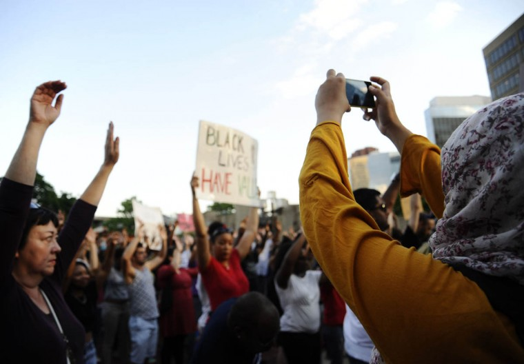 A woman takes a photograph of the crowd as they hold their hands up in a moment of silence at the inner harbor during the solidarity rally and march Thursday evening for Michael Brown of Ferguson, Missouri. (Rachel Woolf/Baltimore Sun)