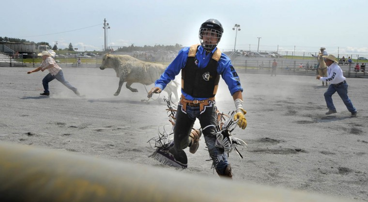 Marshell Warden runs for safety after falling off the bull he was riding at the rodeo. (Lloyd Fox/Baltimore Sun)