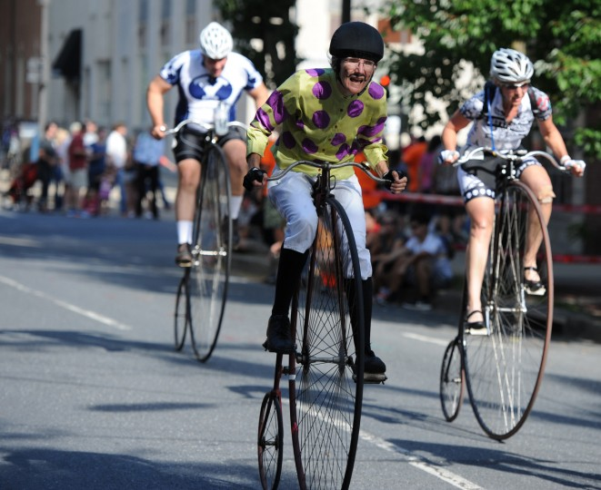 Alison Torpey of Louisville, Ky., who is dressed as a jockey, rides a 1886 Expert Columbia penny farthing or high wheel bicycle in the 2014 Frederick Clustered Spires High Wheel Race. (Kim Hairston/Baltimore Sun)