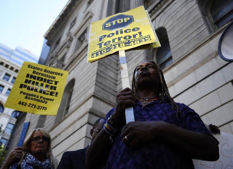 "From left, Donna Plamondon and Lee Patterson, both of Baltimore, hold ""Police Terror"" signs outside of the Clarence Mitchell Jr. Courthouse Thursday evening at the solidarity rally and march for Michael Brown of Ferguson, Missouri. (Rachel Woolf/Baltimore Sun)"