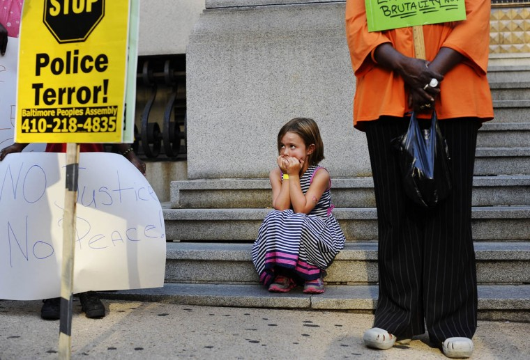 Amelia Vitek, 6, of Baltimore, looks up at protestors and signs outside of the Clarence Mitchell Jr. Courthouse at the solidarity rally and march Thursday evening for Michael Brown of Ferguson, Missouri. (Rachel Woolf/Baltimore Sun)