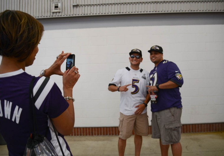 Center, from left, Fernando Talavera, of Laurel, and Javan Camacho, of Jersey City, NJ, pose for a photo before the Ravens game against the San Francisco 49ers at M&T Bank Stadium on August 7, 2014. (Rachel Woolf/Baltimore Sun)