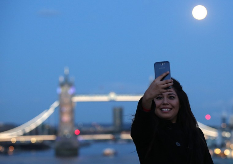 A woman takes a selfie as the supermoon rises over Tower Bridge in London August 10, 2014. The astronomical event occurs when the moon is closest to the Earth in its orbit, making it appear much larger and brighter than usual. (Paul Hackett/Reuters)