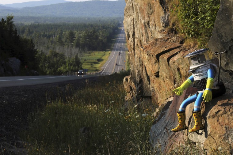 The hitchBOT is seen posed next to Highway 17 north of Sault Ste. Marie, Ontario, and a portion of the Trans-Canada Highway August 5, 2014. The hitch-hiking robot is now at the halfway point in its journey across Canada. (Kenneth Armstrong/Reuters)