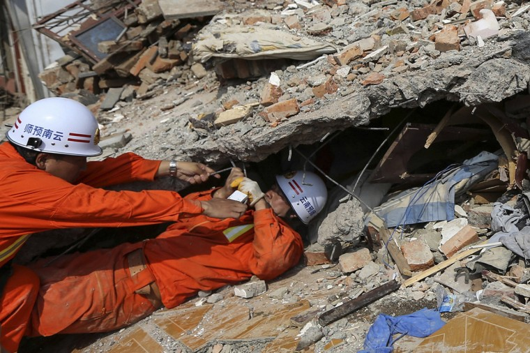 A rescue worker tries to help his colleague to get out from under the debris of a house at the earthquake zone in Longtoushan town, Ludian county, Zhaotong, Yunan province, August 6, 2014. An earthquake in China on the weekend triggered landslides that have blocked rivers and created rapidly growing bodies of water that could unleash more destruction on survivors of the disaster that killed 410 people, state media reported on Tuesday. (Wong Campion/Reuters)