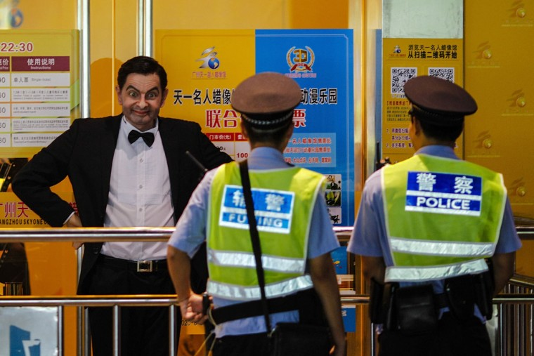 Policemen look at a wax figure of Rowan Atkinson, dressed as his popular television character Mr. Bean, on display outside a wax figure museum in Guangzhou, Guangdong province, August 24, 2014. (Alex Lee/Reuters)