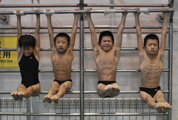 Young divers stretch as they hang from a steel bar during a training session at a sports school in Hefei, Anhui province August 23, 2014. Eleven teenage divers - four girls and seven boys - from the country's rural areas have been training at this school for over two years to prepare themselves for a provincial competition in the coming days. The competition is considered to be their only chance to be picked by the provincial diving team and a gateway to becoming a professional athlete. Picture taken August 23, 2014. (Reuters)