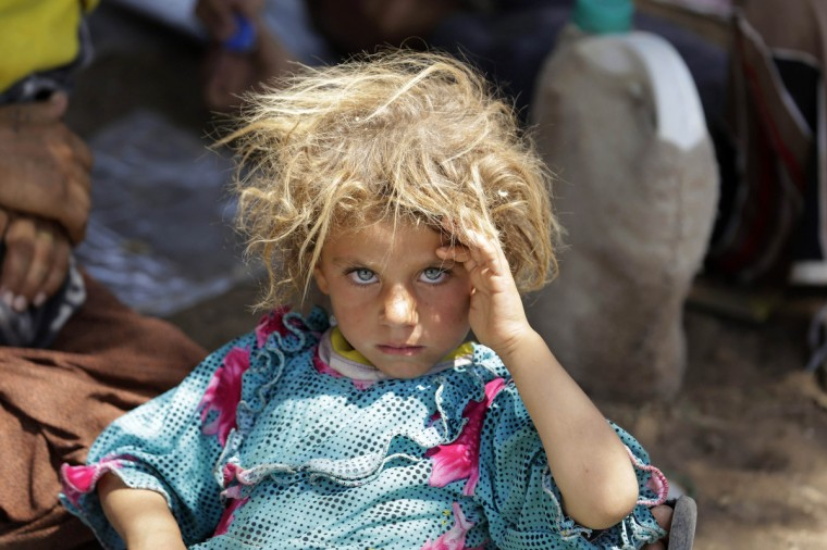 A girl from the minority Yazidi sect, fleeing the violence in the Iraqi town of Sinjar, rests at the Iraqi-Syrian border crossing in Fishkhabour, Dohuk province. (Youssef Boudlal/Reuters)