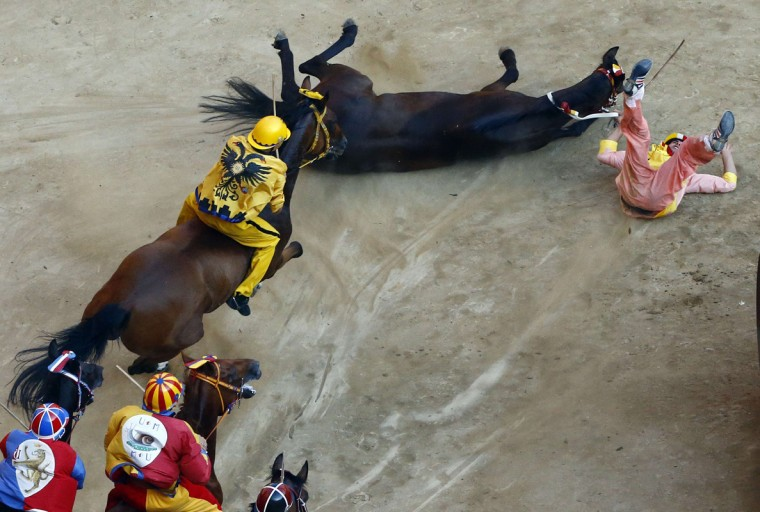"Carlo Sanna, the jockey of ""Valdimontone"" or Ram parish, crashes at the San Martino curve during the Palio of Siena horse race in Siena August 16, 2014. Each July 2 and August 16, almost without fail since the mid-1600s, 10 riders have hurtled bareback around Siena's shell-shaped central square in a desperate bid to win the Palio, a silk banner depicting the Madonna and child. REUTERS/Stefano Rellandini"