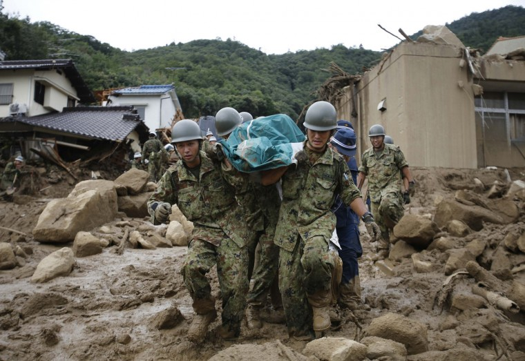 Japan Self-Defense Force (JSDF) soldiers and police officers carry the body of a victim in a plastic bag at a site where a landslide swept through a residential area at Asaminami ward in Hiroshima, western Japan, . At least 27 people, including several children, were killed in Japan on Wednesday, when landslides triggered by torrential rain slammed into the outskirts of the western city of Hiroshima, and the toll was likely to rise, police said. Ten people were missing after a month's worth of rain fell overnight, loosening slopes already saturated by heavy rain over the past few weeks. (Toru Hanai/Reuters)