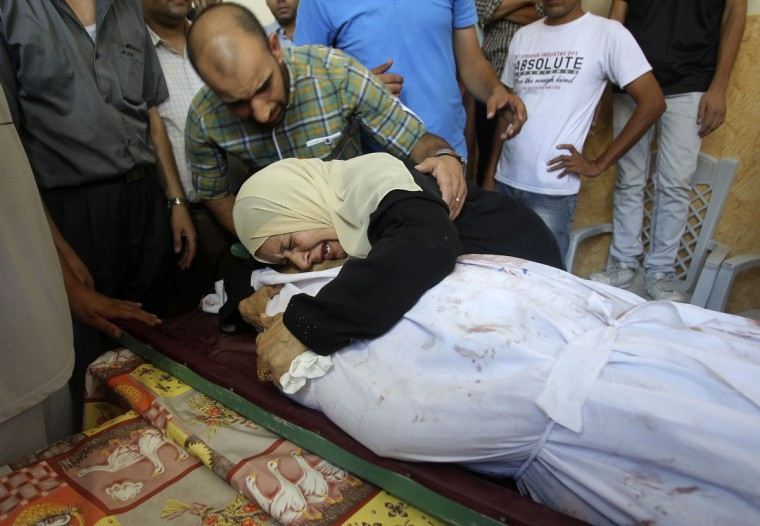 The mother-in-law of Palestinian translator Ali Shehda Abu Afash, whom medics said was killed when unexploded munitions blew up, mourns over his body during his funeral in Gaza City . An Italian journalist, three Palestinian bomb disposal experts, Abu Afash and another person were killed in Gaza on Wednesday when unexploded munitions blew up, medical officials and police said. The explosion occurred in Beit Lahiya, a town in the northern Gaza Strip that had been the scene of fierce fighting between Israeli forces and Palestinian militants during a month-long war. (Ahmed Zakot/Reuters)