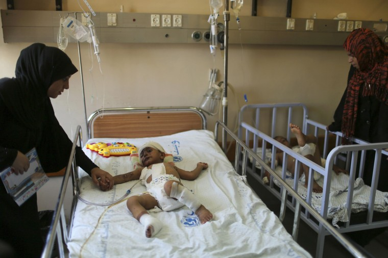One-and-a-half-year-old Palestinian boy Mohammed Wahdan (L), whom medics said was wounded in an Israeli air strike, lies in a bed as he receives treatment at a hospital in Gaza City August 6, 2014. Figures issued on Wednesday by UNICEF, the U.N. children's agency, showed that 419 Palestinian children have been killed in the nearly month-long Gaza war. That compares with 350 children who died in Israel's three-week ground offensive in the enclave five years ago. At least six Israeli children were reportedly injured due to rocket fire from Gaza in the past month, according to preliminary UNICEF figures. Since then, Gaza has been quiet as Palestinians and Israelis observe a 72-hour ceasefire which, it is hoped, will lead to a more durable truce after a war that has devastated much of the densely populated enclave. (Mohammed Salem/Reuters)