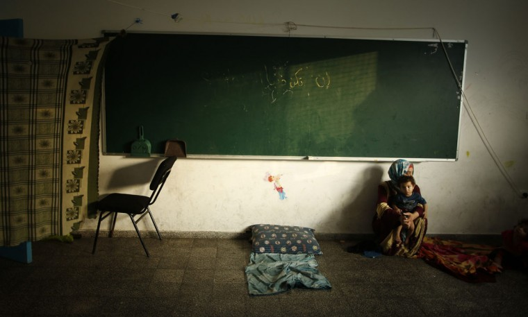 A homeless Palestinian woman holds her son as they stay inside a classroom at a United Nations-run school sheltering displaced Palestinians from the Israeli offensive, in Gaza City August 24, 2014. The Palestinian Ministry of Education said that while 700,000 students in the West Bank will begin the school year on time on Sunday, at least 500,000 students will remain away from classes in the Gaza Strip as the Israeli military offensive on Gaza continues. Israel launched more air strikes on Gaza on Sunday after taking its military campaign to a new level by flattening a 13-story apartment tower following a warning to residents to evacuate. Palestinian militants kept up their cross-border rocket fire in what has become a conflict of attrition that has defied attempts by regional power Egypt to broker a durable truce in fighting now in its seventh week. (Mohammed Salem/Reuters)