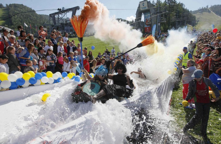 Participants slide down on a chute on a float to cross a 26-meter long pool of water and foam during a competition at the Bobrovy Log Ski Resort near the Siberian city of Krasnoyarsk August 24, 2014. The annual competition marks the end of the short summer season at the Siberian resort. (Ilya Naymushin/Reuters)