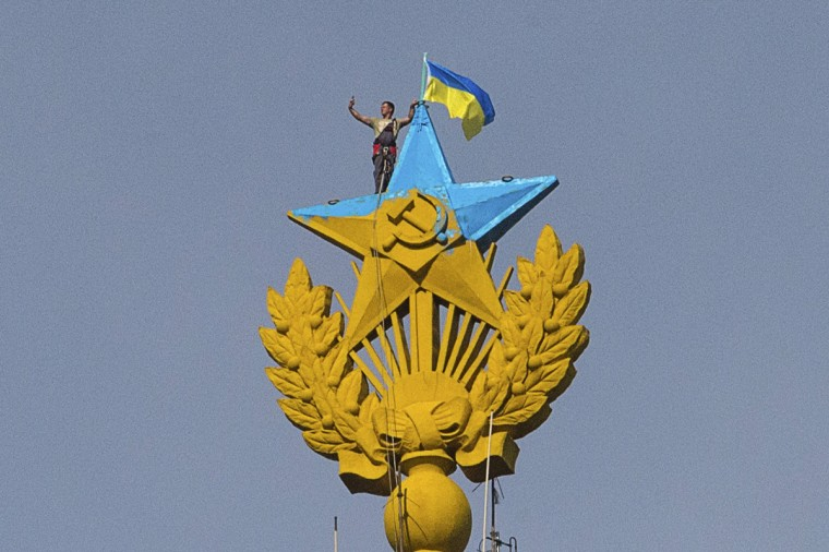 "A man takes a ""selfie"" as he stands with a Ukrainian flag on a Soviet-style star re-touched with blue paint so it resembles the yellow-and-blue national colors of Ukraine, atop the spire of a building in Moscow. Russian police said on Wednesday they had charged four young people with vandalism after they climbed to the top of a Moscow skyscraper and briefly attached a Ukrainian flag to its spire. (Ilya Varlamov/Reuters)"
