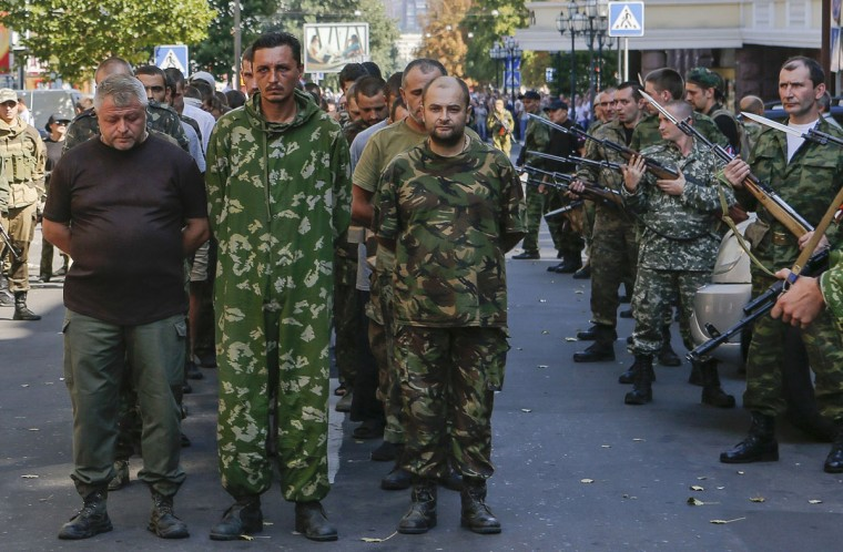 Armed pro-Russian separatists (R) escort a column of Ukrainian prisoners of war as they walk across central Donetsk August 24, 2014. Pro-Russian separatist rebels force-marched dozens of Ukrainian prisoners of war along the main street of the rebel-held Ukrainian town of Donetsk on Sunday. (Maxim Shemetov/Reuters)