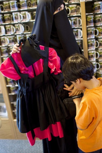 Haya Almekemi and Moaath, 5, visiting from Kuwait, shop for an example of Amish girls' clothing at a gift shop within the Amish Experience, a tourism destination in the village of Bird-in-Hand, Pennsylvania August 9, 2014. (Mark Makela/Reuters)