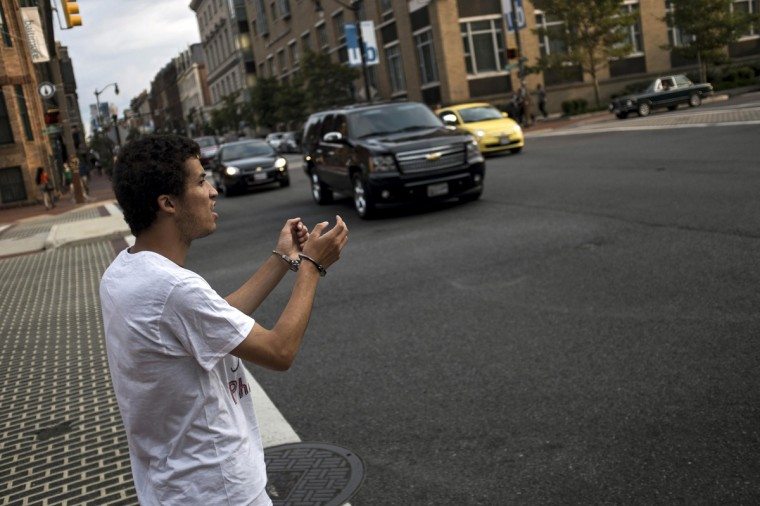 Brandon Wallace, 27, protests by wearing handcuffs before a community meeting with city officials about new youth curfew legislation going into effect on August 8 at the University of Baltimore Law Center in Baltimore Tuesday July 29, 2014. Baltimore, faced with high crime rates, is set to impose one of the strictest U.S. curfews for young people, with the mayor facing residents on Tuesday to explain the new rules. (James Lawler Duggan/Reuters)