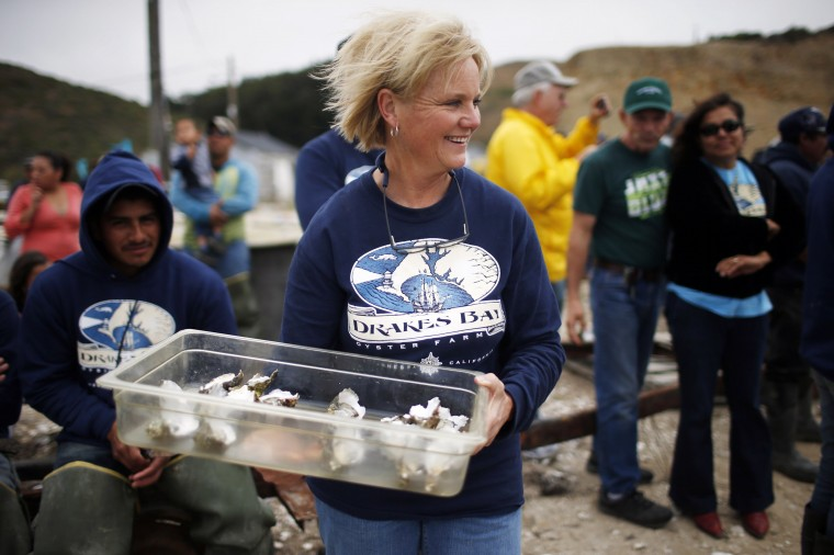 Ginny Lunny-Cummings, farm manager at Drakes Bay Oyster Company, carries a tray of oysters for a toast during a celebration ceremony to recognize the company in Inverness, California July 31, 2014. (Stephen Lam/Reuters)