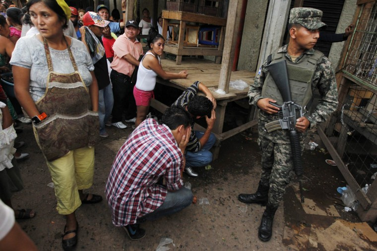 Onlookers stand by as friends mourn for a young man who was shot amidst what local media claimed are accusations of extortion from vendors at a market in Tegucigalpa August 26, 2014. Honduras and Nicaragua are among the most impoverished in the Americas, but Honduras is also blighted with the world's highest murder rate, at 90.4 homicides per 100,000 people, according to the United Nations, while Nicaragua's rate is just 11.3. (Jorge Cabrera/Reuters)