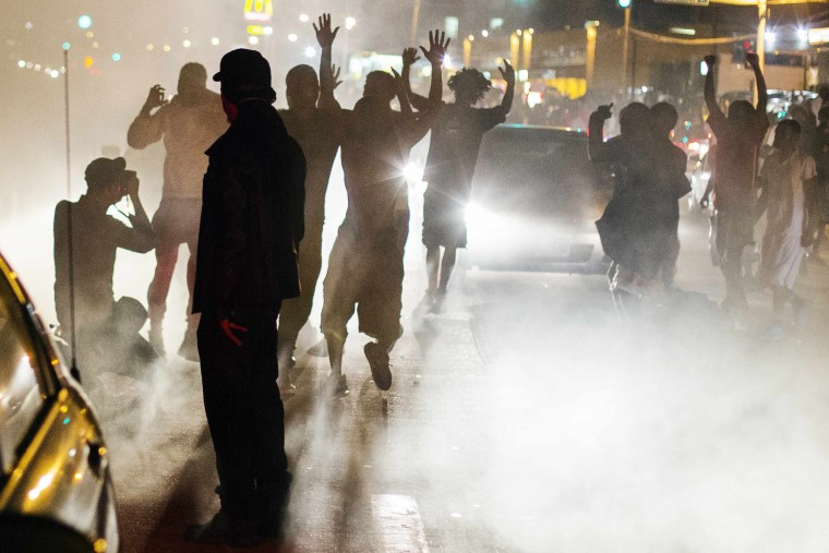 Protesters chant during a peaceful demonstration as communities continue to react to the shooting of Michael Brown in Ferguson, Missouri August 15, 2014. Missouri's governor Jay Nixon moved to ease tensions on Thursday after days of racially charged protests over the police shooting of Brown, an unarmed black teenager, putting the African-American captain of the Highway Patrol Ron Johnson in charge of security in the St. Louis suburb of Ferguson. (Lucas Jackson/Reuters)