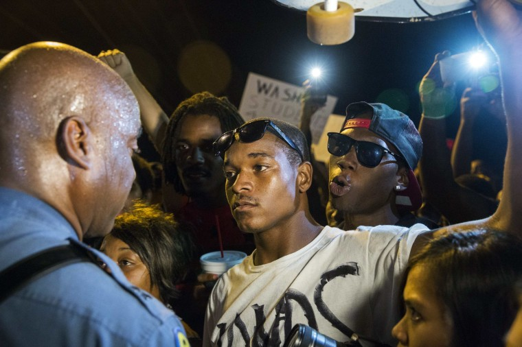 Missouri State Highway Patrol Captain Ron Johnson (L) speaks to protesters as he walks through a peaceful demonstration as communities continue to react to the shooting of Michael Brown in Ferguson, Missouri August 14, 2014. Missouri's governor Jay Nixon moved to ease tensions on Thursday after days of racially charged protests over the police shooting of Brown, an unarmed black teenager, putting the African-American captain of the Highway Patrol Johnson in charge of security in the St. Louis suburb of Ferguson. (Lucas Jackson/Reuters)