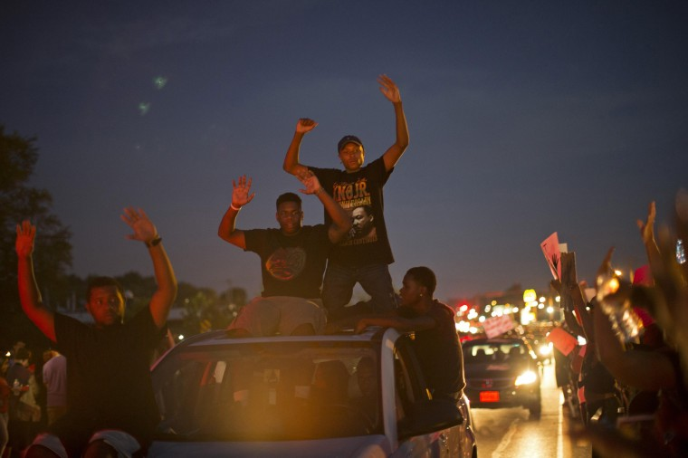 People raise their hands as they drive by during a peaceful demonstration, as communities react to the shooting of Michael Brown in Ferguson, Missouri August 14, 2014. Missouri's governor Jay Nixon moved on Thursday to calm days of racially charged protests over the police shooting of Brown, an unarmed black teenager, naming the African-American captain of the Highway Patrol Ron Johnson to oversee security in the St. Louis suburb of Ferguson. (Mario Anzuoni/Reuters)