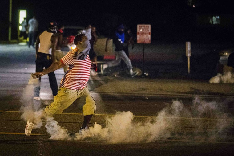 A protester picks up a gas canister to throw back towards the police after tear gas was fired at demonstrators who are continuing to react to the shooting of Michael Brown in Ferguson, Missouri August 17, 2014. Shots were fired and police shouted through bullhorns for protesters to disperse, witnesses said, as chaos erupted Sunday night in Ferguson, Missouri, which has been racked by protests since the unarmed black teenager was shot by police last week. (Lucas Jackson/Reuters)