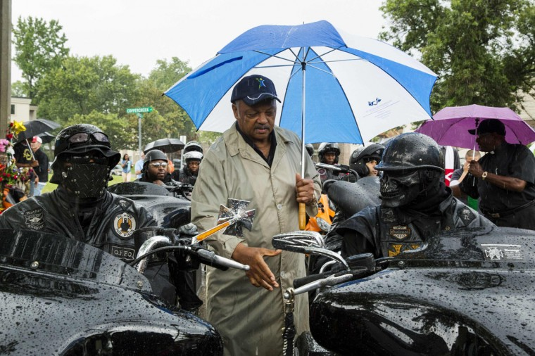 "Civil rights leader Jesse Jackson (C) greets members of the ""Outcast"" motorcycle club before a vigil in the neighborhood where teenager Michael Brown was shot, in Ferguson, Missouri, August 16, 2014. Tensions had temporarily cooled on Thursday night but by Friday evening, protesters were again swarming through a residential and retail district in the small town outside St. Louis that has become the site of repeated clashes between protestors and police forces. The unrest erupted after Ferguson police officer Darren Wilson, 28, shot and killed Brown shortly after noon last Saturday as Brown and a friend walked down a street that runs through an apartment complex where Brown's grandmother lives. REUTERS/Lucas Jackson"