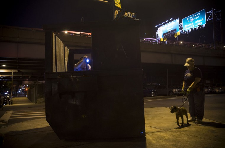 Richard Reynolds (L), a founding member of the Ryders Alley Trencher-fed Society, uses a flashlight to look for rats in a dumpster as Judy (R) and her Border Terrier Merlin stand by, ready to make a kill, during an organized rat hunt on New York's Lower East Side July 25, 2014. The Ryders Alley Trencher-fed Society (R.A.T.S.) is a group of enthusiasts who take their dogs out to hunt rats in New York City. Members of the independent group venture out on night-time excursions to allow their dogs to do what they do best: hunt and kill vermin. (Mike Segar/Reuters)