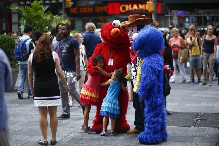 "Jorge, an immigrant from Mexico, poses with children while dressed as the Sesame Street character Elmo in Times Square, New York July 30, 2014. Elmo and Cookie Monster have long delighted young viewers on TV's ""Sesame Street,"" but the recent antics of New York street performers dressed as the beloved characters have drawn the ire of city officials and now the show's producers. Sesame Workshop, which owns the rights to Big Bird, Ernie and the assorted puppet monsters on the 45-year-old program, said on July 29, 2014 it was drafting plans to stop performers who dress up as the characters from appearing in Times Square, where they pose for photos with tourists and then demand tips. Picture taken July 30, 2014. (Eduardo Munoz/Reuters)"