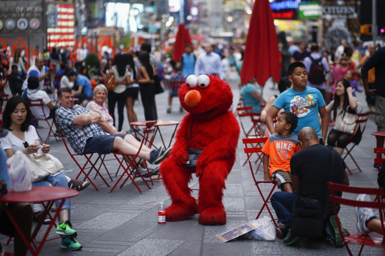 Jorge, an immigrant from Mexico, dressed as the Sesame Street character Elmo rests in Times Square, New York July 29, 2014. (Eduardo Munoz/Reuters)