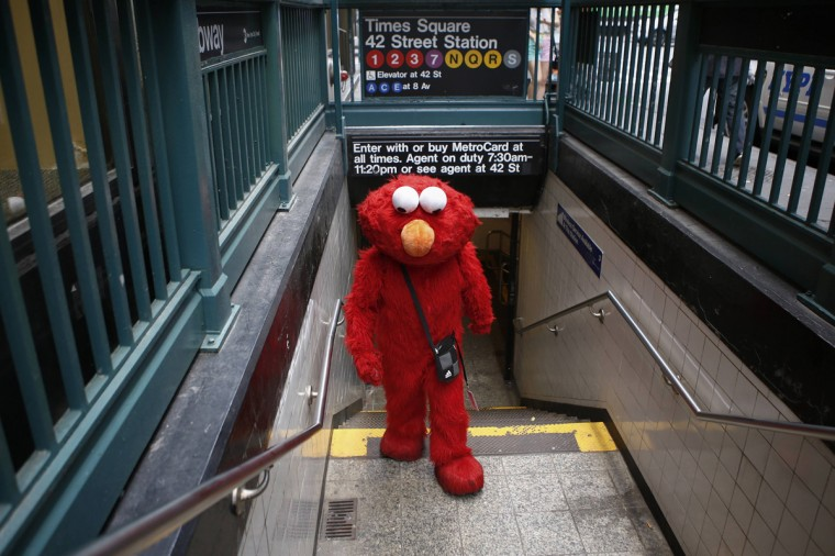 Jorge, an immigrant from Mexico, exits a subway station dressed as the Sesame Street character Elmo in Times Square, New York July 30, 2014. (Eduardo Munoz/Reuters)