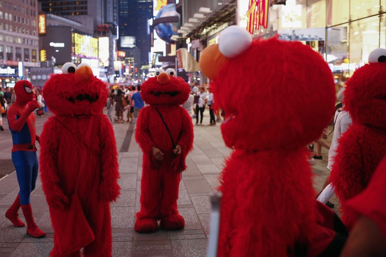 Jorge, an immigrant from Mexico (C), stands amidst other people, all dressed as the Sesame Street character Elmo, while they look to make tips for photographs in Times Square in New York July 30, 2014. (Eduardo Munoz/Reuters)
