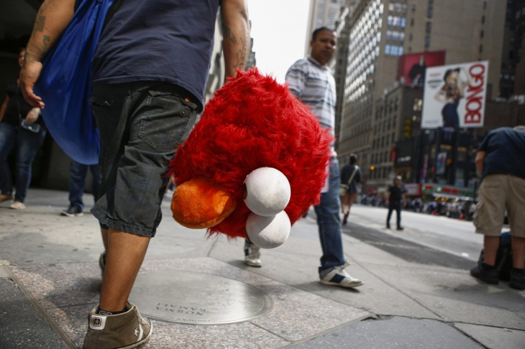 Jorge, an immigrant from Mexico, carries the head of the Sesame Street character Elmo while he walks through Times Square, New York July 30, 2014. (Eduardo Munoz/Reuters)