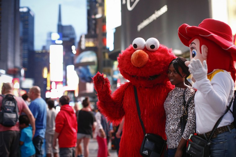 Jorge, an immigrant from Mexico, poses with a woman while dressed as the Sesame Street character Elmo in Times Square, New York July 29, 2014. (Eduardo Munoz/Reuters)