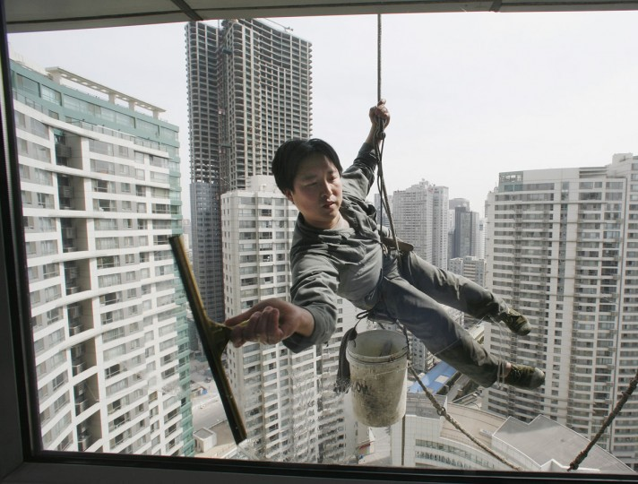 A worker cleans the windows of an apartment block in Beijing's central business district April 4, 2007. (REUTERS/Reinhard Krause)