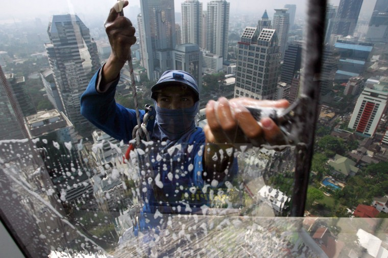 A worker cleans the window of a building in Bangkok on January 22, 2009. (REUTERS/Sukree Sukplang)