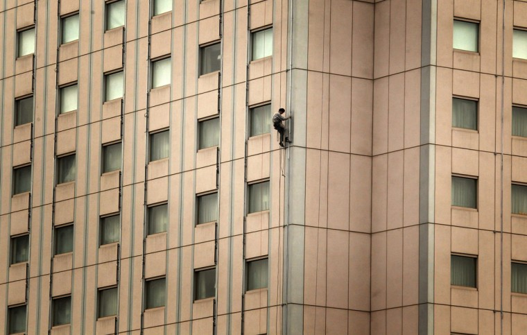 A cleaner abseils down the side of a newly renovated building in central Beijing on March 5, 2012. (REUTERS/David Gray)