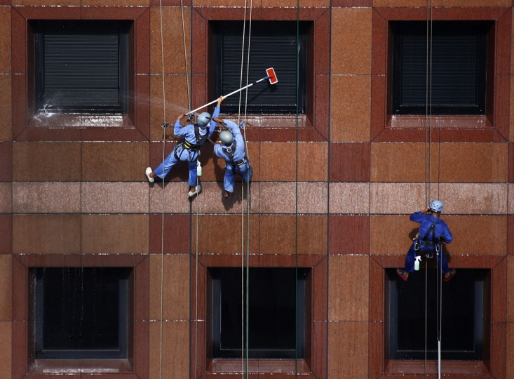 Window cleaners hang from the facade of Ngee Ann City shopping mall in Singapore on January 9, 2014. (REUTERS/Petar Kujundzic)