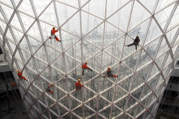 "Workers clean the exterior of the ""Sun Valley"" at the 2010 World Expo site in Shanghai on October 10, 2009. (REUTERS/China Daily)"
