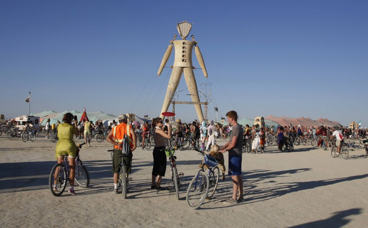 "People gather at the man structure during the Burning Man 2014 ""Caravansary"" arts and music festival in the Black Rock Desert of Nevada, August 27, 2014. People from all over the world have gathered at the sold out festival to spend a week in the remote desert cut off from much of the outside world to experience art, music and the unique community that develops. (Jim Urquhart/Reuters)"